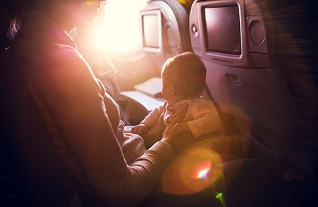 Ouder met kind in een vliegtuigstoel