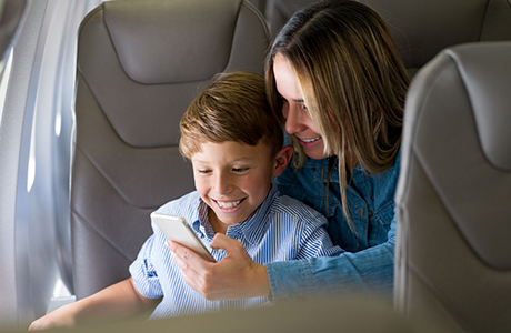 Mor med barn på smartphone på fly