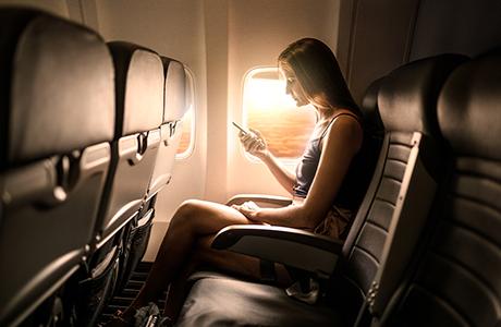 Kvinde på fly med smartphone